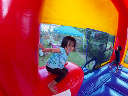 Happy kids jumping in inflatable bouncer Oahu Hawaii